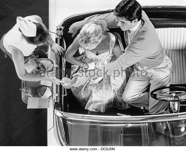 1950s DRIVE IN RESTAURANT CARHOP WAITRESS ON ROLLER SKATES SERVING COUPLE 1955 T