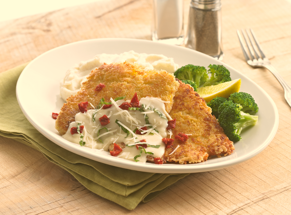 Parmesan Crusted Chicken - Our marinated chicken breasts coated with Parmesan cheese and crunchy Panko bread crumbs, lightly pounded and pan fried to a golden brown. Served with white cheddar mashed potatoes and steamed broccoli, and topped with a lemon Chardonnay butter sauce, sun-dried tomatoes, fresh basil and Parmesan cheese. #cheese #parmesan #chicken #dinner #winnerwinnerchickendinner