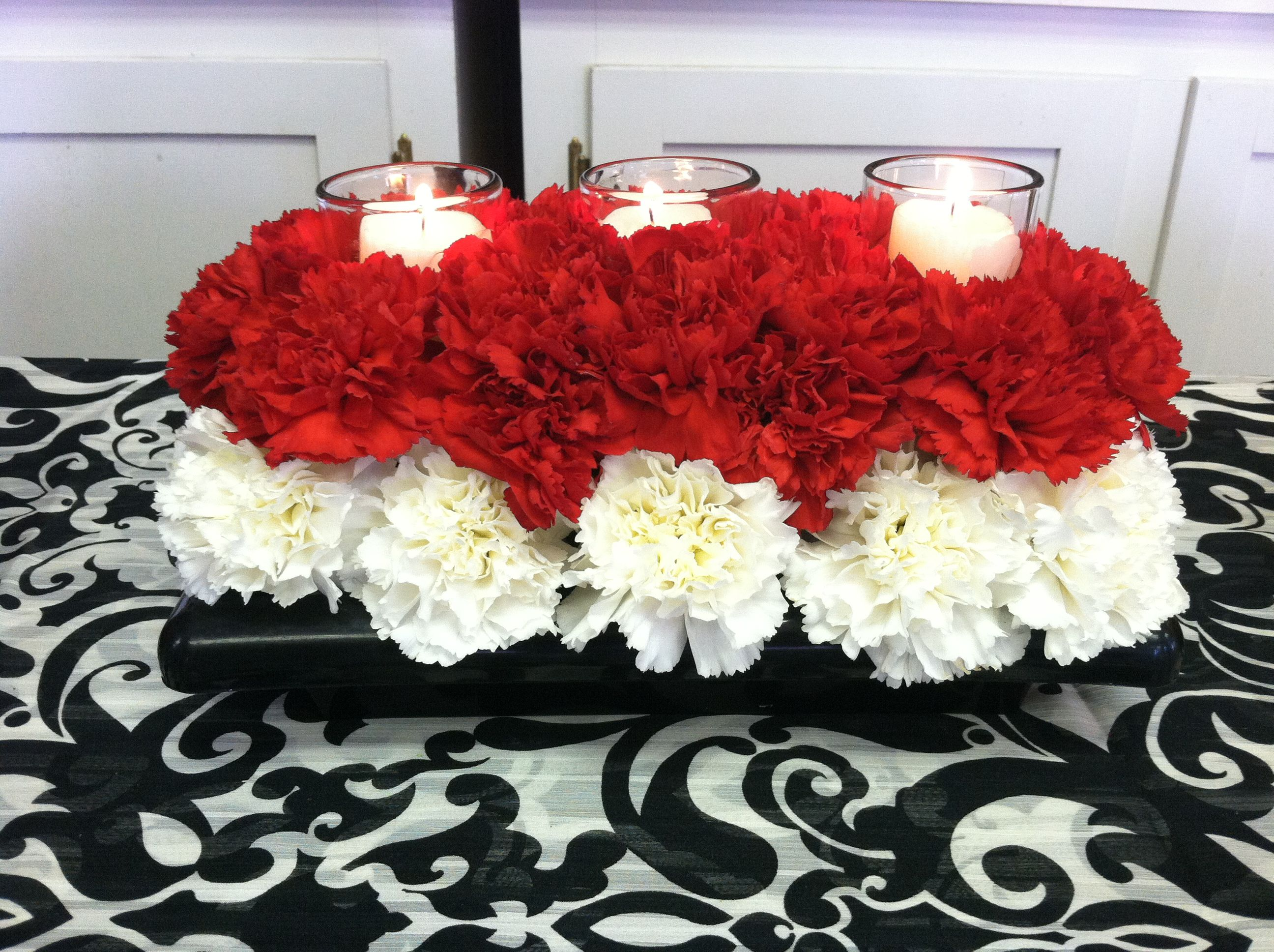 Red and white carnation centerpiece with candles perfect