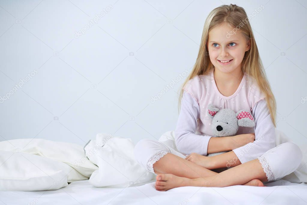 Little Girl In The Bedroom Is Sitting On The Bed Little Girl Is