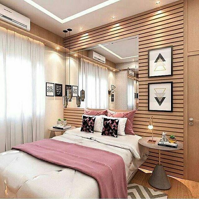 Quarto com parede em madeira ripada, mesa lateral, espelho de cabeceira e quadros, luminária pendente e tapete gráfico cinza e branco. Spots com iluminação gesso rebaixado.