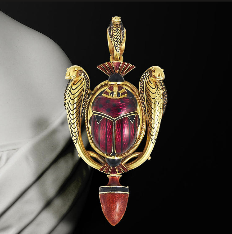 An archaeological revival gold and enamel brooch/pendant, by Robert Phillips, circa 1865  Set to the centre with a raised scarab rendered in scarlet guilloché enamel with black enamel spot and stripe detail, between a pair of finely modelled rearing gold cobras with black enamel decoration, suspended from a detachable gold and black enamel coiled cobra suspensory loop, terminating with a later burnt sienna guilloché enamel amphora drop, glazed compartment to reverse