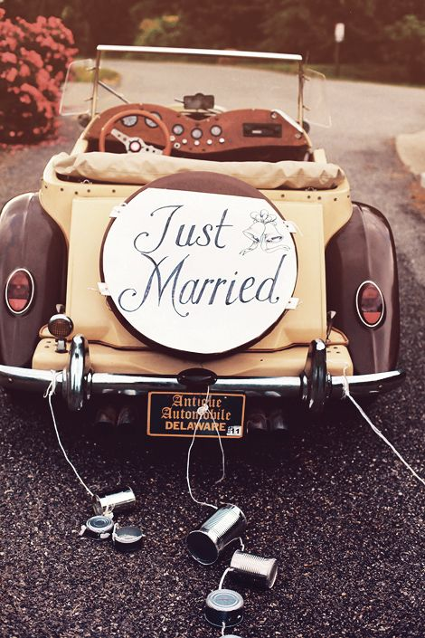 Antique Brown Car With A Just Married Sign With Tin Cans From