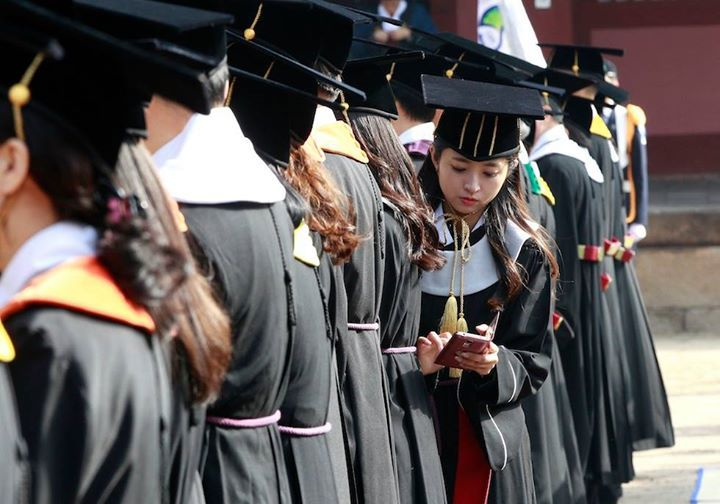 Una ragazza controlla lo smartphone durante la cerimonia di laurea all'università di Sungkyunkwan a Seul Corea del Sud (AP Photo/Ahn Young-joon)