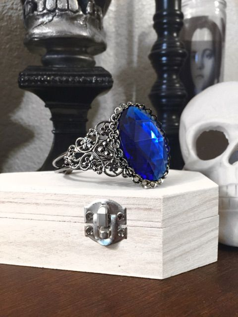 """Spirit+of+an+ICE+QUEEN+is+a+gunmetal+adjustable+cuff+bracelet+featuring+a+sapphire+blue+gem.+Part+of+the+""""Captured+Spirits""""+collection.  <br>  Products+take+7-12+business+days+to+produce,+and+will+be+shipped+shortly+after.+Thank+you!"""