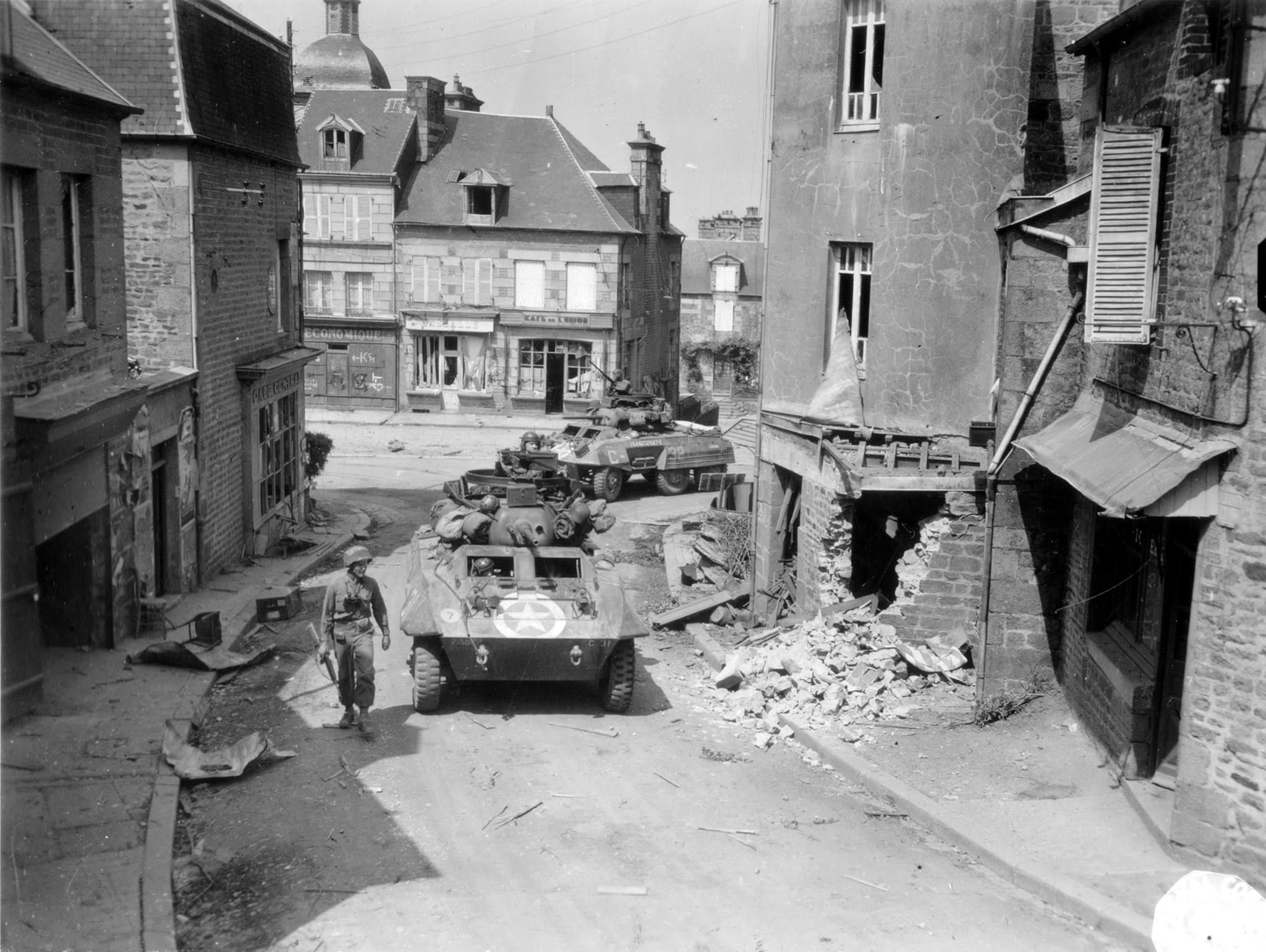 A pair of M8 Armoured Cars of 'C' Company, 82nd Recon Battalion, 2nd Armored Division, pass through Saint Sever Calvados, on 3rd August 1944.