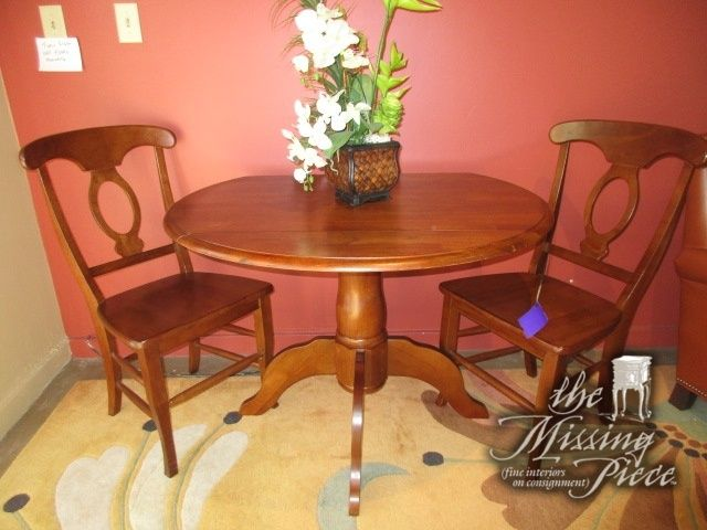 """Traditional style dropleaf table with two chairs in a medium finish. Perfect set for a smaller dining area or kitchenette. Measures 42""""long x 26""""wide; (2)8""""leaf. Makes a 42""""round table with leaves up. Quite nice."""