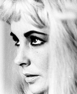 Elizabeth Taylor poses wearing a blonde wig, 1963.