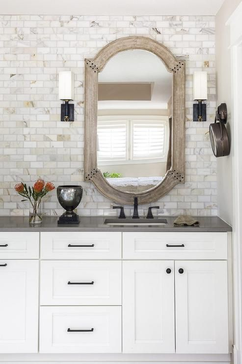 Chic Bathroom Features A White Washstand Adorned With Oil Rubbed Bronze Hardware Topped With Gray Qua White Bathroom Cabinets Wood Tile Bathroom White Bathroom