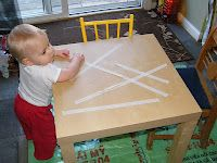 Toddler Activities - peeling tape off the table (or fridge) develops fine motor skills (lots of ideas here).