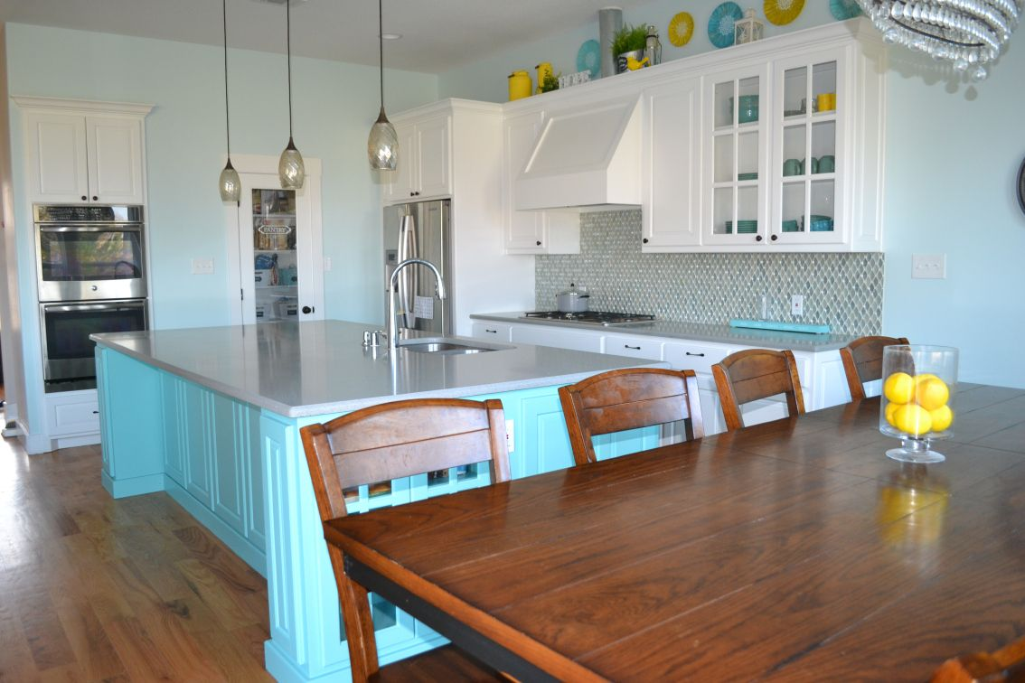 White kitchen cabinets with teal island, walk in pantry ...
