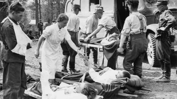 Haavoittuneita suomalaisia sotilaita hoidetaan sidontapaikalla. SA-kuva.
