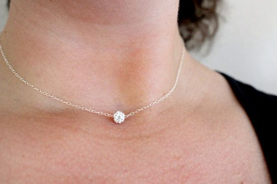 A sparkling crystal ball has been set on delicate sterling silver chains to make this dainty short modern necklace.