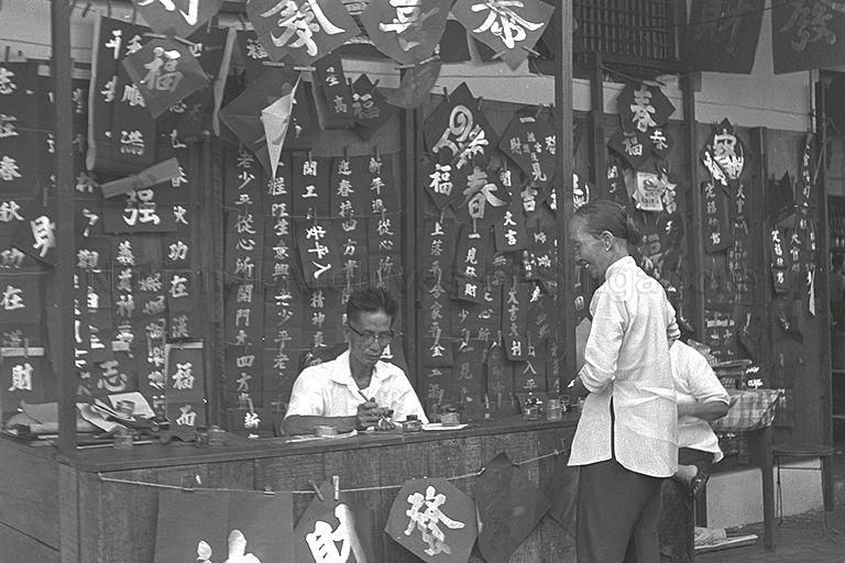 SCENE AT CHINATOWN ON EVE OF CHINESE NEW YEAR. MAN WRITING