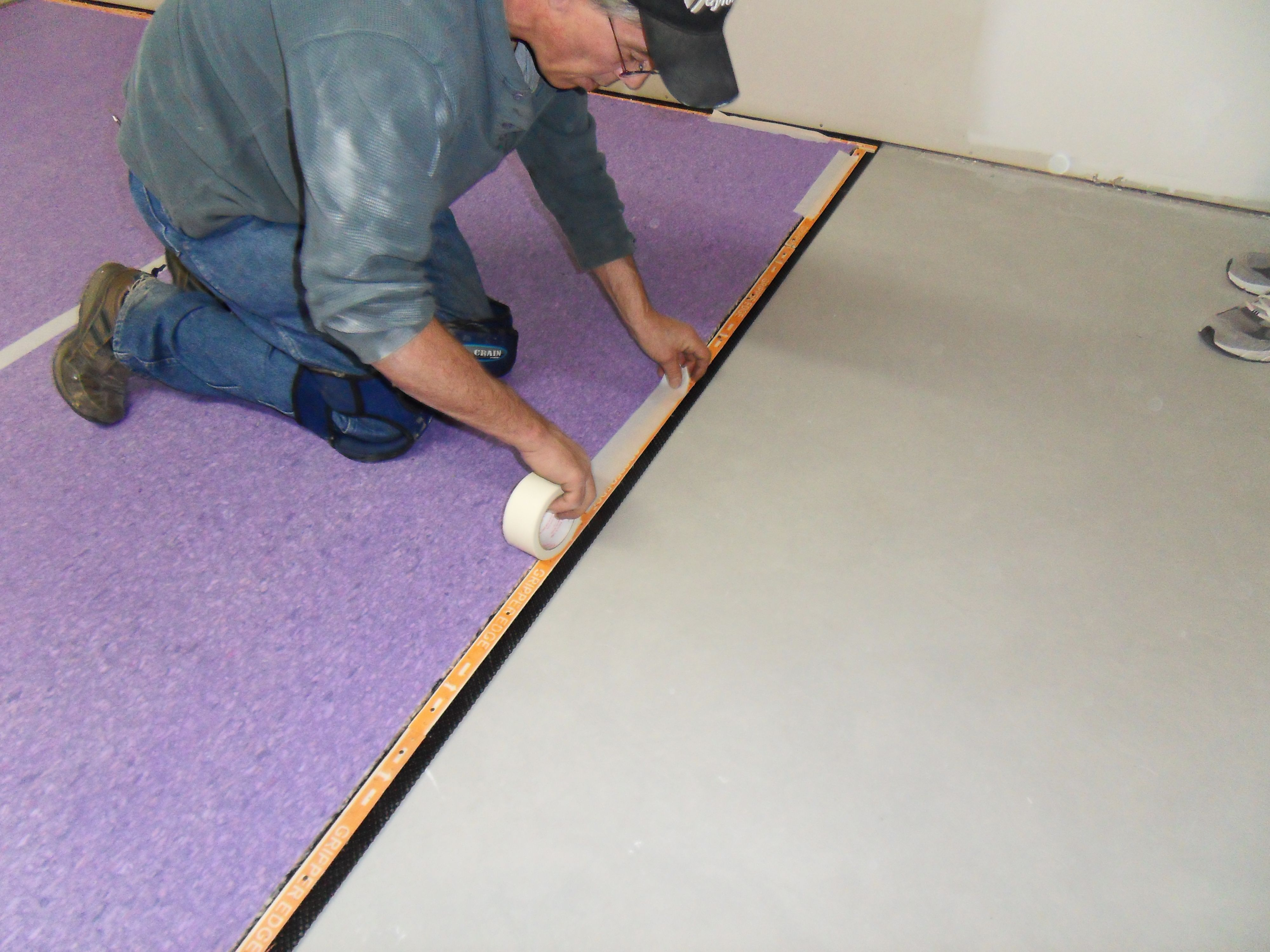 SUPERSEAL's Carpet Subfloor - Taping the carpet pad in place.