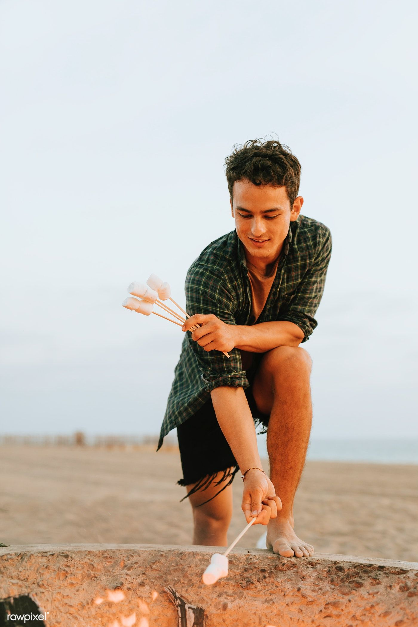 Download premium image of man roasting marshmallows over a