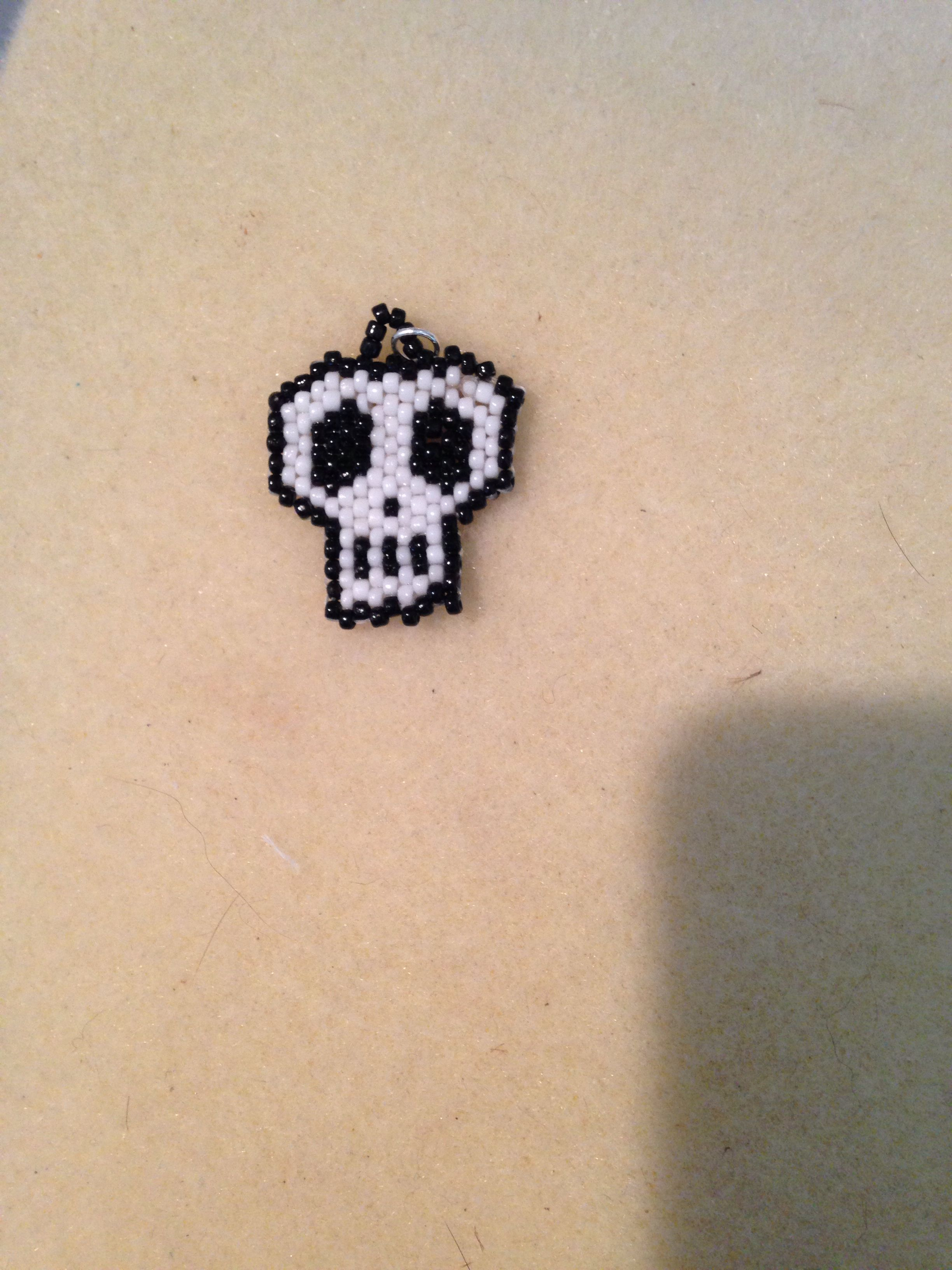 """Skull pendant done by me granddaughter Brebre.  1""""square,done in seed beads. Not bad for her first brick stitch project."""