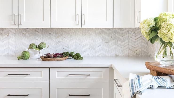 Then marble backsplash tiles features silver and white herringbone pattern that stands out with a trending finish accenting white shaker cabinets and quartz countertops. #whiteshakercabinets Then marble backsplash tiles features silver and white herringbone pattern that stands out with a trending finish accenting white shaker cabinets and quartz countertops. #whiteshakercabinets Then marble backsplash tiles features silver and white herringbone pattern that stands out with a trending finish acce #whiteshakercabinets