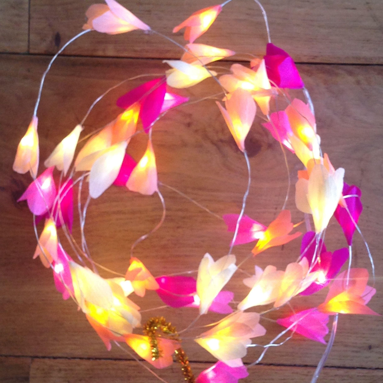 guirlande de 50 led lumineuse, lumière blanc chaud. Décorée de pétale de fleur en papier: blanc, écru, rose pâle, rose, et fuchsia. La guirlande est alimentée par pile AAA. La guirlande fait 5m de long