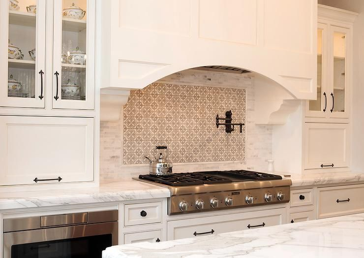 an arched white wood hood is mounted to marble mini brick backsplash rh pinterest com