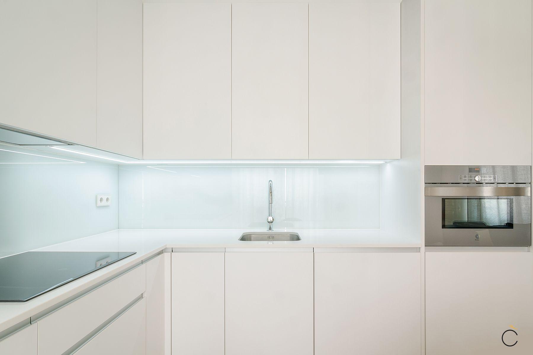 Cocina blanca con luces Led debajo de los muebles altos para ...