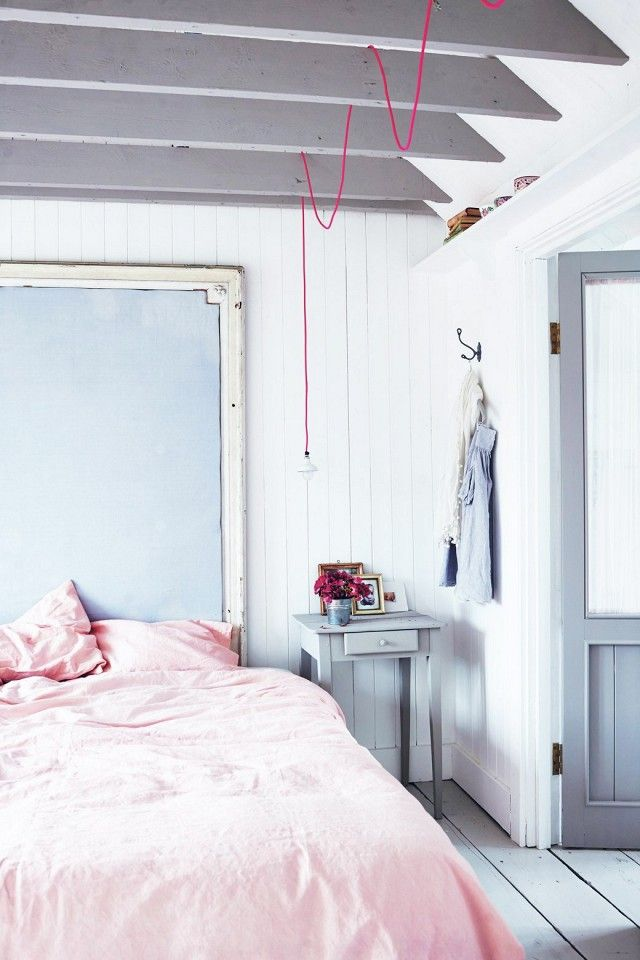 Pastel colored bedroom with white washed walls, pink bedding, and a bare light bulb