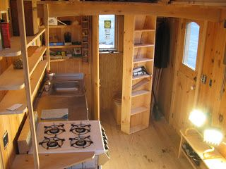 gold thread tiny house nearing end of construction kitchen along side wall bathroom and closet along end wall showing open closet door with built in