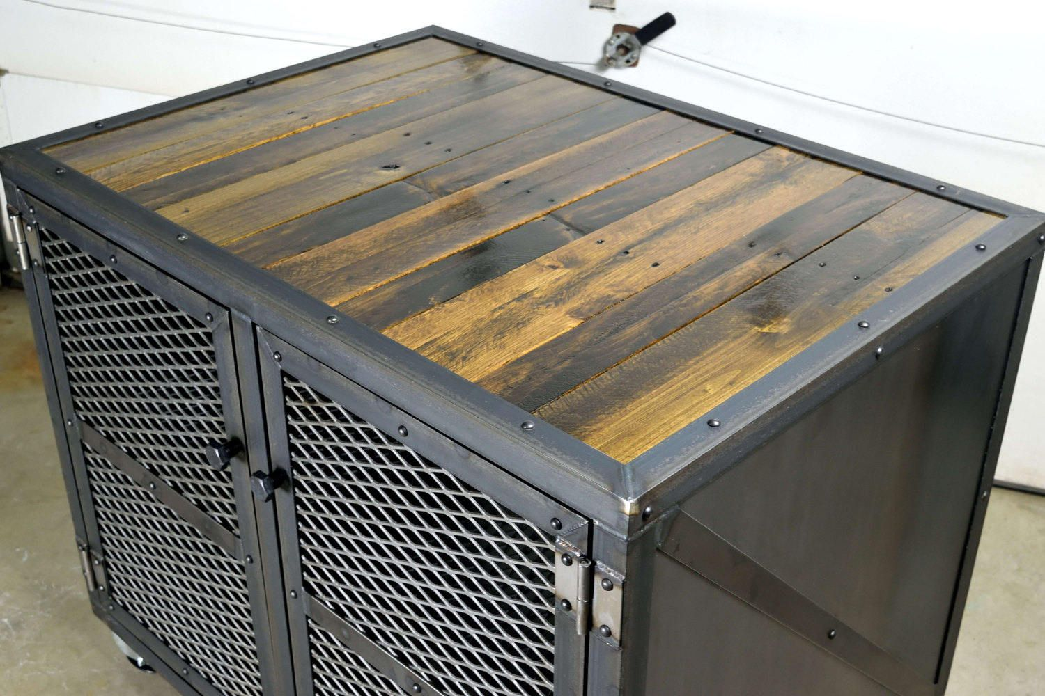Industrial Kitchen Island Bar  Storage Cabinet is part of Industrial furniture Islands - This Unique piece of industrial furniture is crafted from hot rolled steel, reclaimed oak and pine, expanded metal and steel casters  All of the Woodwork and Fabrication Cutting, grinding, welding, drilling, riveting and construction is done by hand, one part at a time  This custom made industrial cabinet would work great as a Kitchen Island, Bar Cart or any other storage cabinet  It features 2 doors on each side and a shelf about halfway up that runs throughout  The steel has a hand applied wax finish to prevent rust but preserve the look of raw steel  The wood has a durable multi coat polyurethane finish  This piece can be made with wood in place of any of the steel panels or any configuration of door styles  Dimensions 42 x30 x35 tall PLEASE CONTACT ME FOR A FREIGHT QUOTE BEFORE PURCHASE!!!!  Buyer is responsible for all shipping costs  Local pickup available The piece shown has been sold but another one can be made as is or modified to your custom specifications  CUSTOM ORDERS ARE ENCOURAGED!! Need a different size  Different finish  Other materials  If you can think of it I'm sure I can make it! Feel free to contact me with any questions or inquiries and I will reply as soon as I can!!