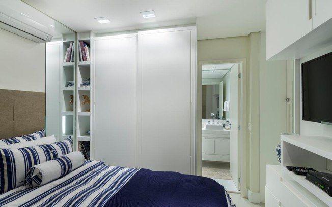 Mais espelhos no quarto. Aqui, em formato vertical ao lado da cama, eles alongam o ambiente. Repare na marcenaria que ocupa todos os cantos