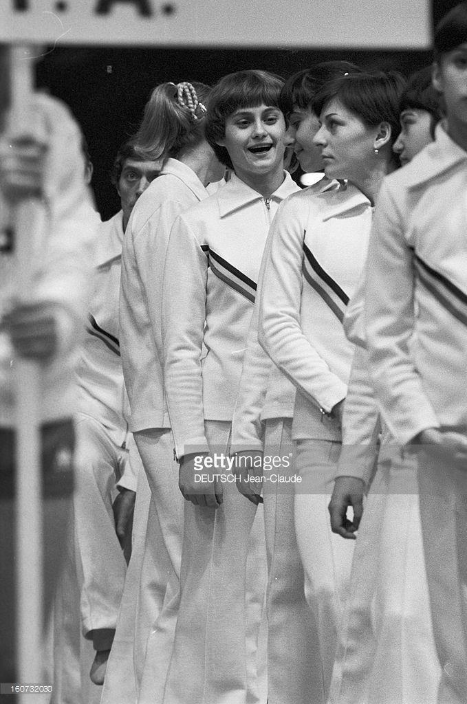 World Championships Of Artistic Gymnastics From 1978 To Strasbourg. A Strasbourg, en 1978, lors des XIXèmes championnats du monde de gymnastique artistique, dans le stade couvert, parmi l'équipe roumaine féminine, rangée en file indienne et portant des suvêtements aux couleurs du pays, Nadia COMANECI, souriant et parlant avec ses coéquipières.
