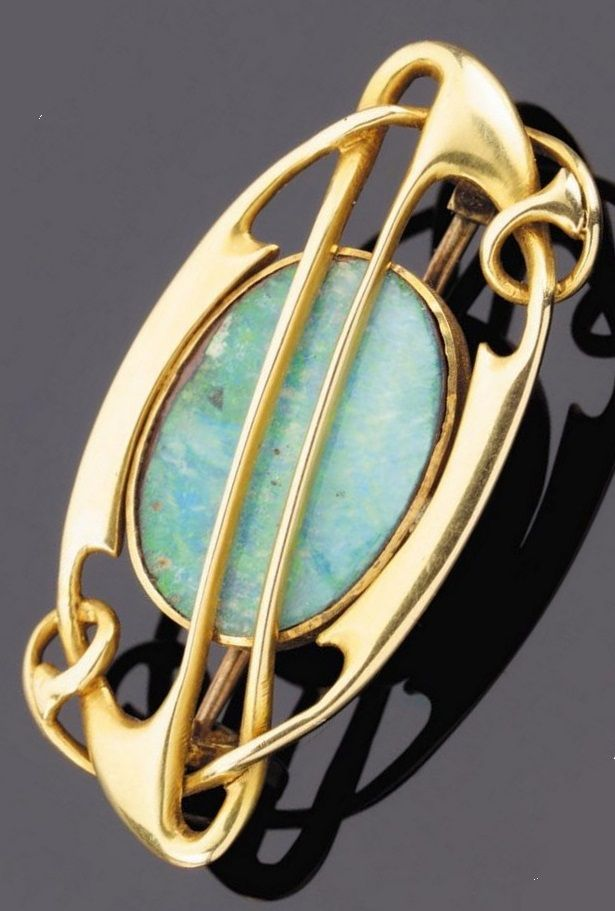 AN ART NOUVEAU GOLD AND OPAL BROOCH, BY ARCHIBALD KNOX FOR LIBERTY & CO., CIRCA 1900. The oval stone within a whiplash mount, 3.5cm. long.