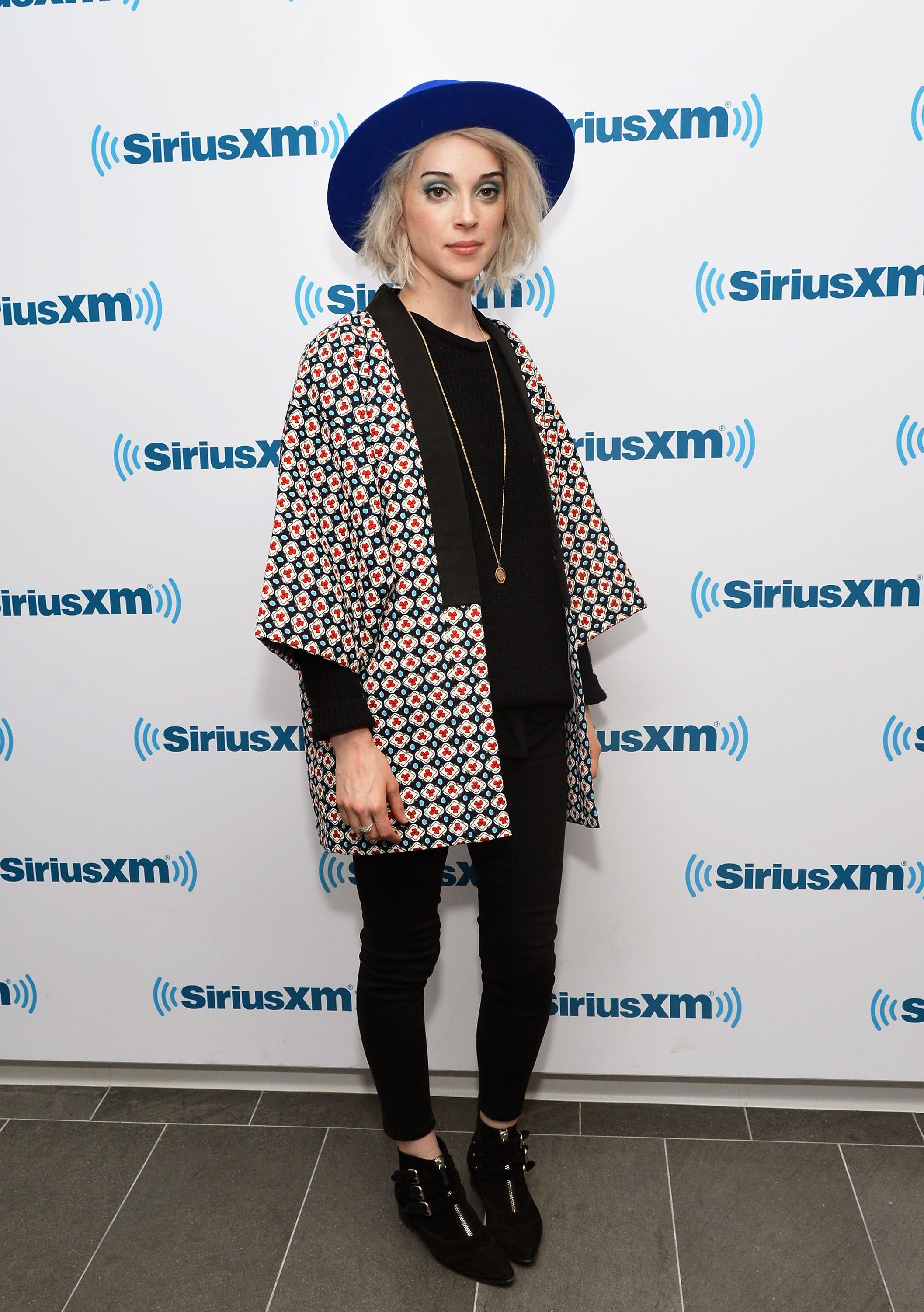 Wearing all-black, St. Vincent pairs an origami-like geometric coat with a wide-brimmed royal blue boater hat for an unexpected pop of color.   - MarieClaire.com