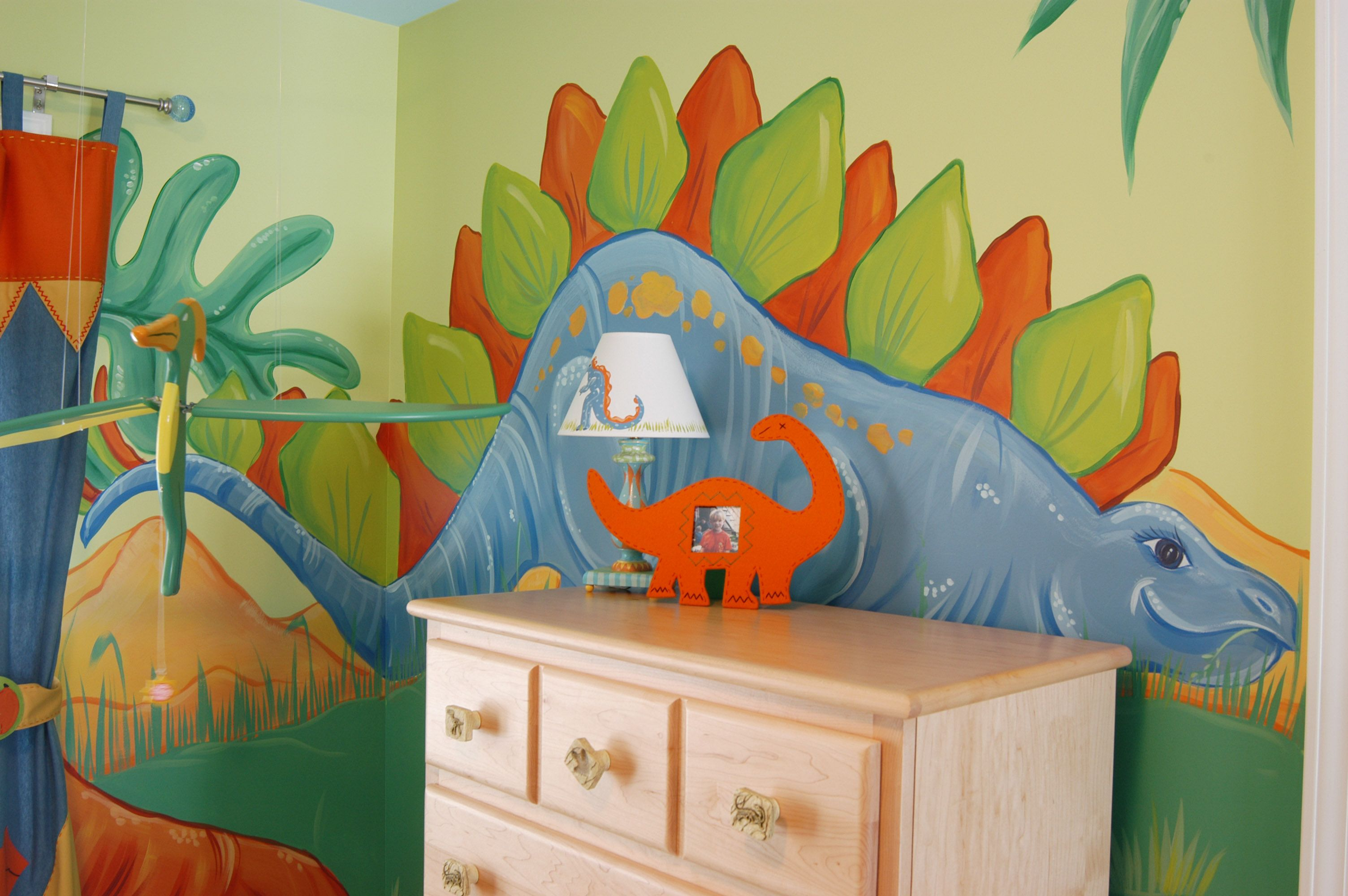 A Friendly Dinosaur Mural And Cloud Ceiling To Compliment The