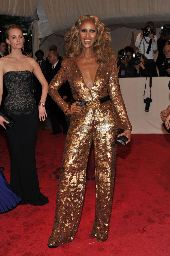 Iman Jumpsuit - Iman sparkled at the 2011 Met Gala in a low-cut gold sequined jumpsuit with a black satin belt.