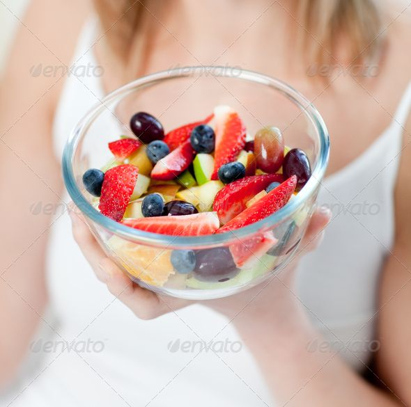 Close-up of a caucasian woman eating a fruit salad ...  adult, appetite, apple, attractive, beautiful, berry, blueberries, bowl, breakfast, bright, caucasian, charming, cheerful, color, delighted, dessert, diet, dish, eat, eating, female, food, fresh, fruit, fruits, glowing, happiness, happy, health, healthy, healthy eating, home, interior, jolly, joyful, lifestyle, living-room, lunch, meal, nutrition, orange, positive, pretty, radiant, salad, smile, smiling, tasty, vitality, woman