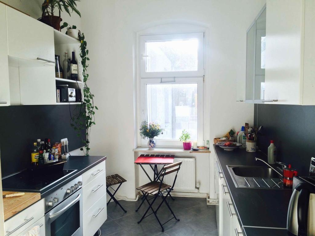 Schöne moderne Küche mit dunklem Fliesenboden und viel Lichteinfall ...