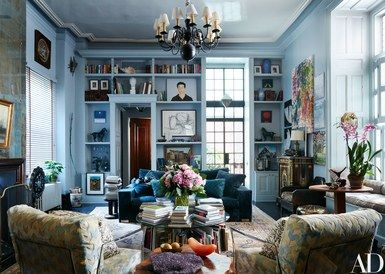 Painted in Benjamin Moore's Whale Gray, Jack Pierson's living room walls and shelves brim with beloved art, books, and objects. The artist worked with designer Fernando Santangelo to create rooms in his Greenwich Village apartment that call to mind a timeless New York style | archdigest.com