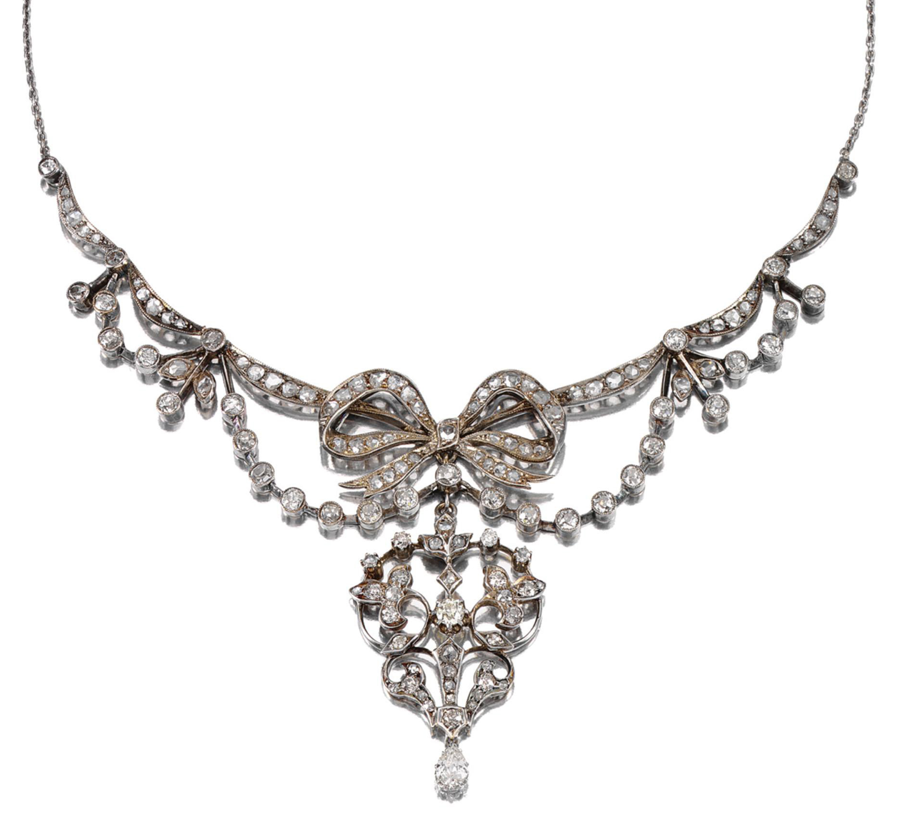 DIAMOND PENDANT NECKLACE, LATE 19TH CENTURY The central ribbon bow motif framed by foliate swags and suspending an open work pendant terminating on a pear-shaped diamond drop, set throughout with circular- and rose-cut diamonds, to a trace link chain, length approximately 430mm, composite, later chain, case.