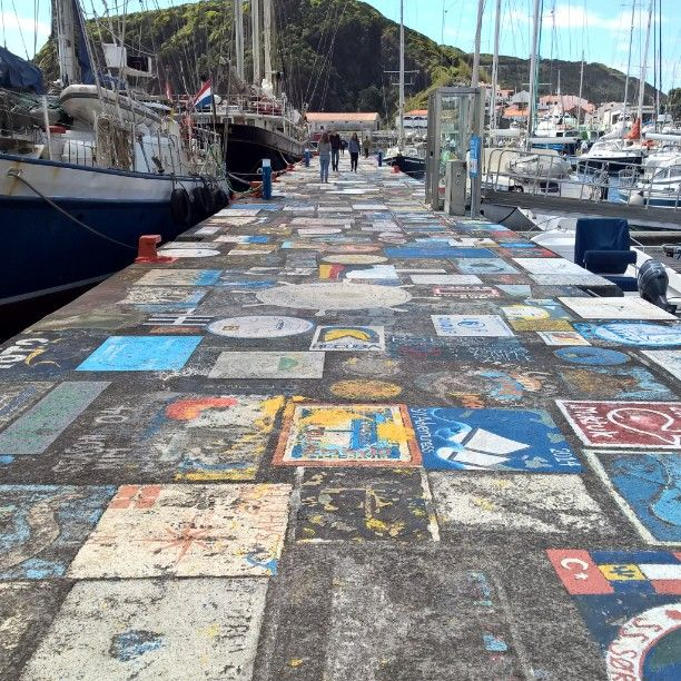 Faial harbor dock. Every sailor that pass through Faial island, Azores, traditionally has to paint something for good luck. Azores islands are the gate for sailors crossing Atlantic to East, from Carribean to Europe. It has been for centuries. Now the sailor are mostly skippers of sailboat. Photograph @Massimobassano #natgeophoto #Azores #Faial #whalewatching #skipper #sailing