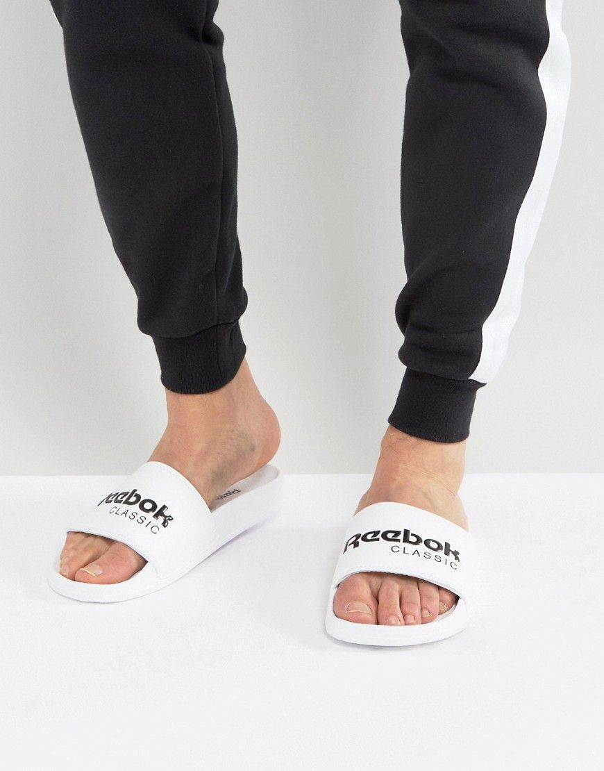 ca0c338387ffe5 Get this Reebok s basic sneakers now! Click for more details. Worldwide  shipping. Reebok Classic Sliders In White BS7417 - White  Sandals by Reebok