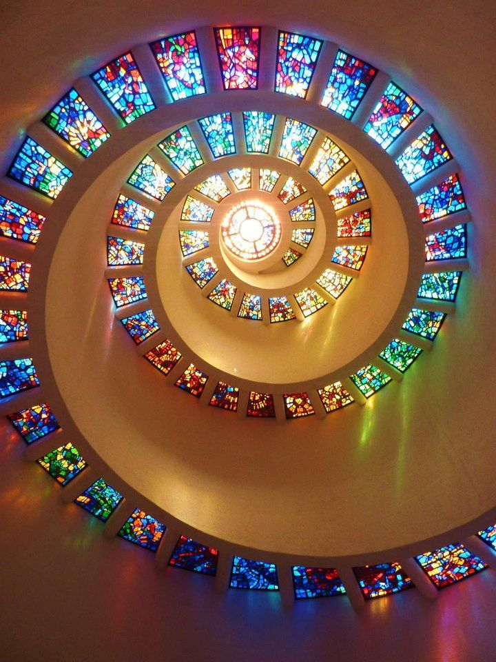 """""""Glory Window""""  The most prominent and recognizable feature of Thanks-Giving Square is the Chapel of Thanksgiving, a small, spiral tower that features an enclave for prayerful thanks. The entrance to the chapel is at the end of a 125-foot bridge that runs over a cascading waterfall. Inside the chapel, the spiral is topped with stained glass """"Glory Window"""", one of largest horizontally mounted stained-glass pieces in the world."""