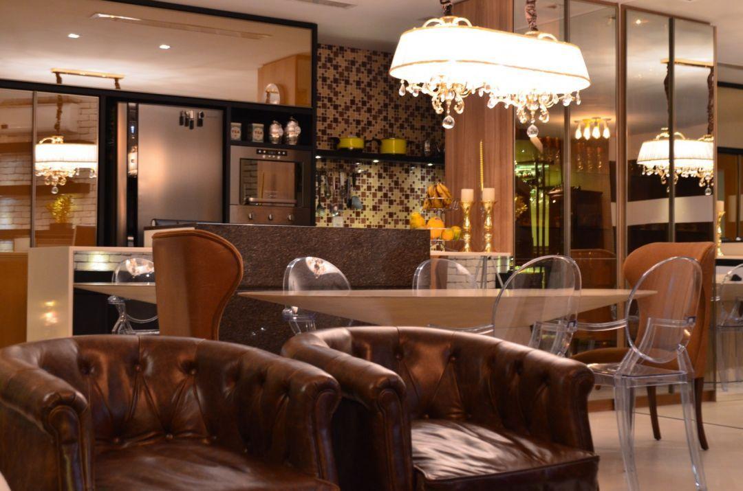 HELENAROCHAarquitetura - Sala de jantar com mesa oval e cadeiras altas em destaque nas extremidades e as demais mais discretas no entorno. Cozinha de fundo. Lustre pendente longitudinal.