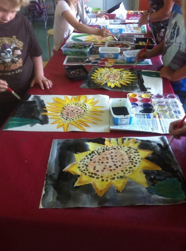 """""""Auringonkukkia"""". Ensin piirrettiin keskustan ympyrät vapaalla kädellä ja maalattiin vesiväreillä. Sitten tuputettiin pulloväreillä kynää käyttäen siemenet. Lehdet ja terälehdet liituväreillä ja tausta lopuksi vesiväreillä. (Ilona Hackzell / Alkuopettajat -FB -sivustosta)"""
