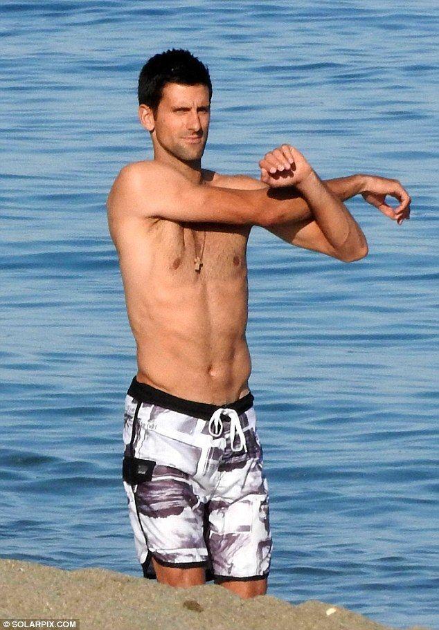 Shirtless Novak Djokovic relaxes on a beach in Marbella