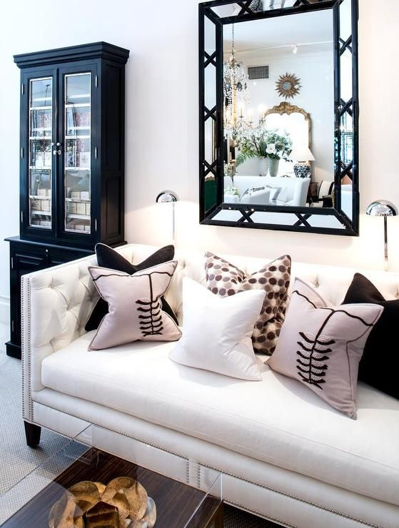 Chic Living Room Features A Black Bamboo Mirror Over White Tufted High Back Sofa With Silver Nailhead Trim Adorned Pink And Pillows Flanked By