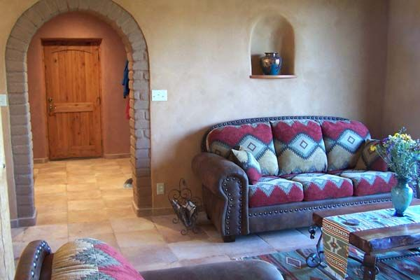 a southwest style interior this adobe house in Arizona has exposed adobe bricks, earthen plasters and tiled floors.
