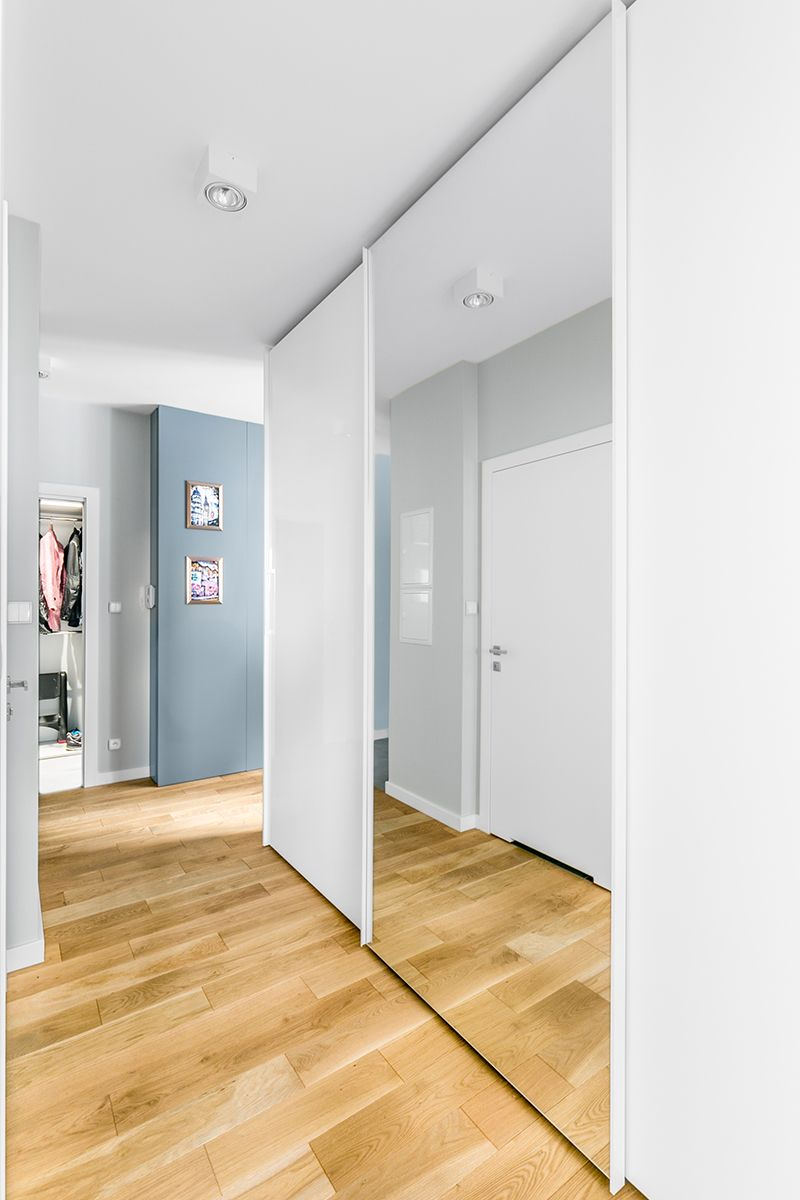Natural Wood Floor With White Built In Wardrobe Sliding Door With