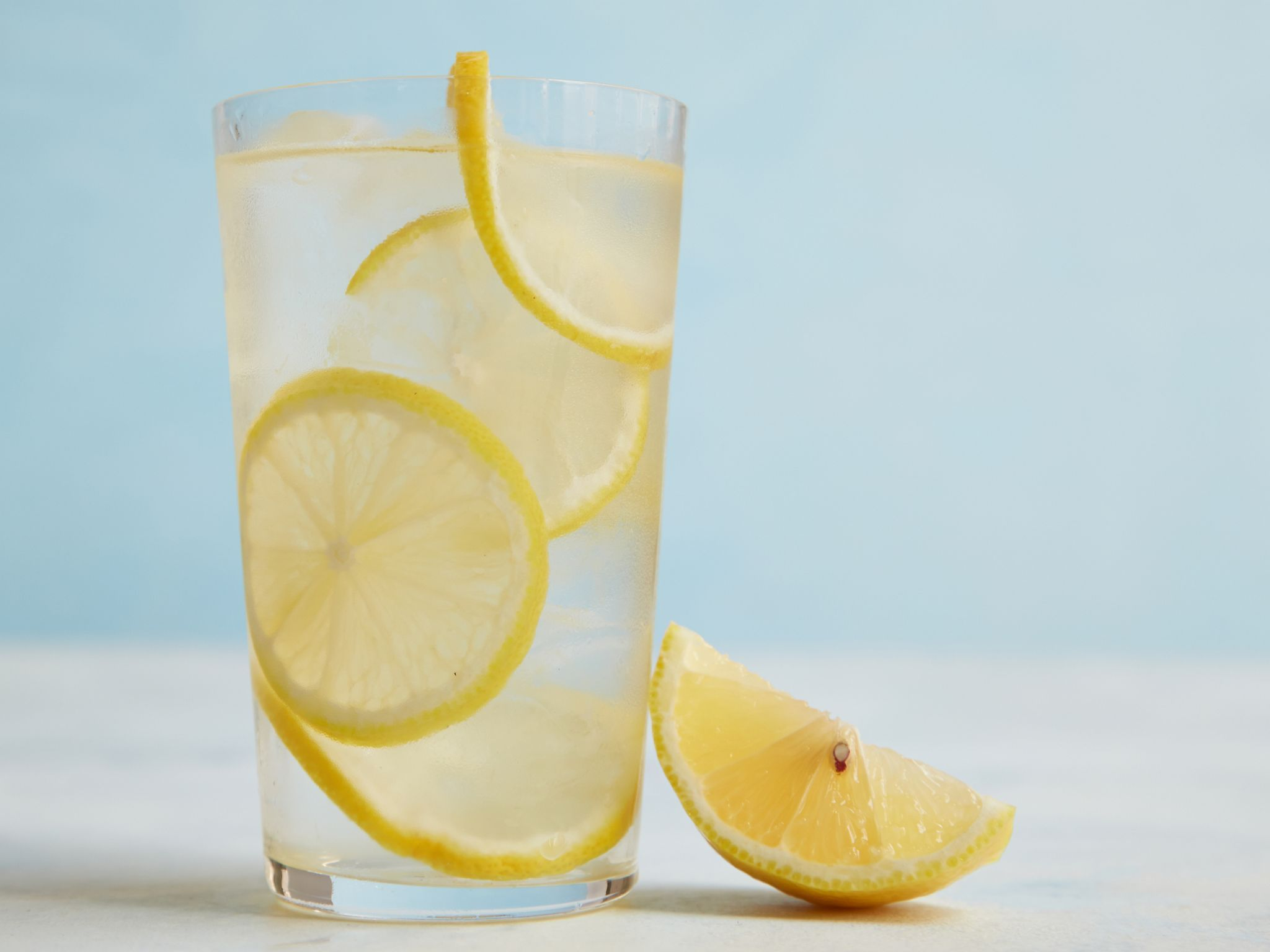 Lemoninfused water squeezing a wedge of lemon into a