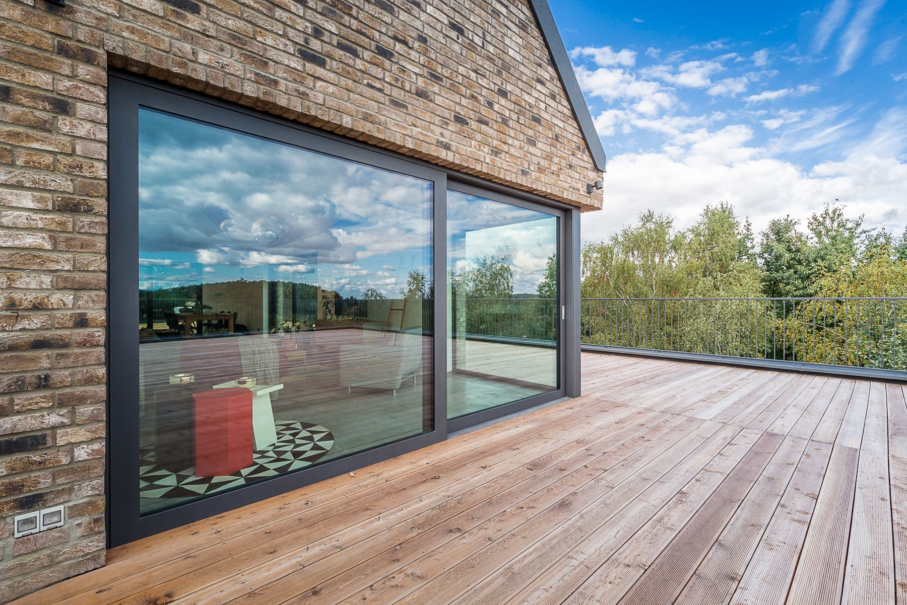une jolie façade de maison grâce au contraste de la baie vitrée
