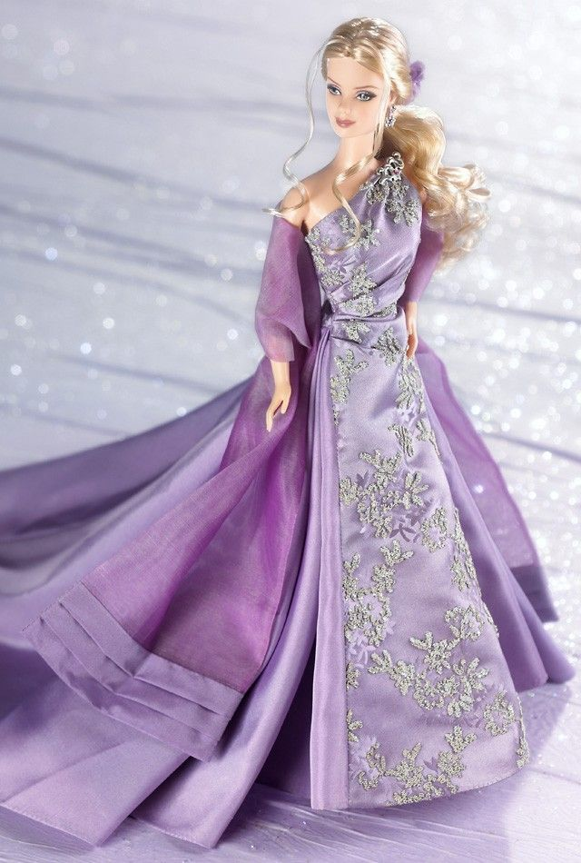 """Barbie® doll 2003 wears a lavender gown that goes over one shoulder to create an elegant look. The bodice of the gown has shiny, silvery caviar beading. She also wears a dark lavender organza floor length wrap trimmed at the bottom with taffeta. Her hair is pulled back into an elegant low ponytail that is curled on the bottom. She wears silvery flower dangle earrings. Her rhinestone brooch reading """"2003"""" is on the shoulder of the gown."""